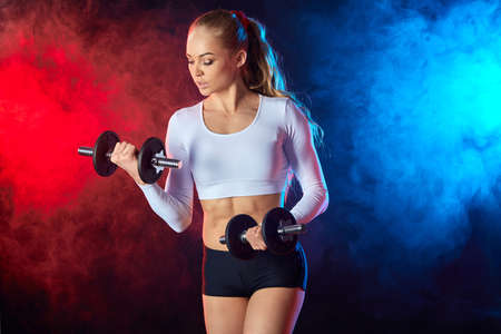 serious woman in stylish sportswear working out with dumbbells in the sport club. close up side view photo. wellness, wellbeing, body care 版權商用圖片