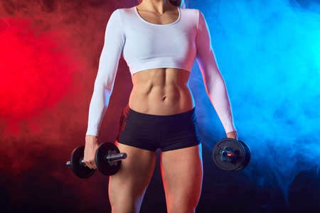 strong muscular woman holding dumbbells and posing to the camera. well-built female athelete with flat stomach