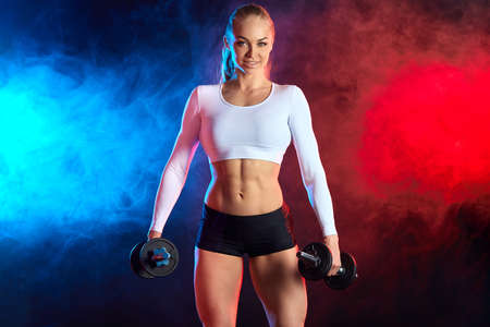 cheerful sportswoman in white top and black shorts leads healthy lifestyle. isolated black background, red and blue smoke