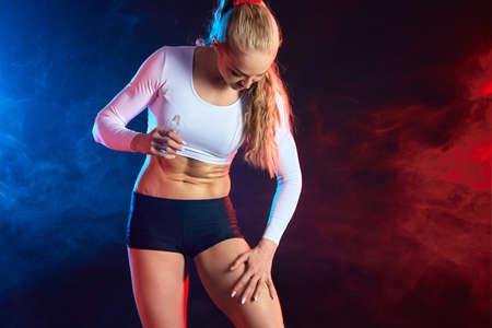 blonde sportswoman touching soft fresh skin isolated on black background.