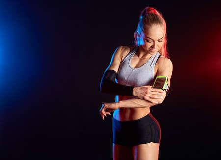 beautiful runner athlete listening to music from handphone armband. close up photo