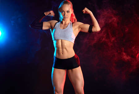 awesome pleasant strong woman with raised arms showing her musculars. close up photo. hobby, interest