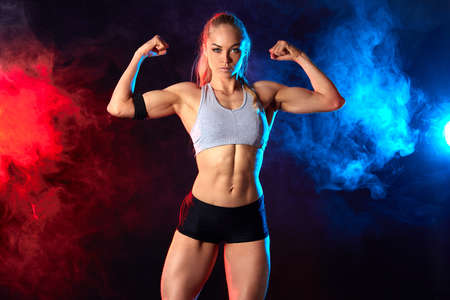 attractive female athlete is good at sport, woman leads healthy lifestyle. isolated black nbackground with redand blue smoke