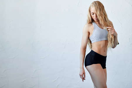 well-built slim fit girl in stylish sportswear standing over white background. sport and fitness, motivation concept. copy space