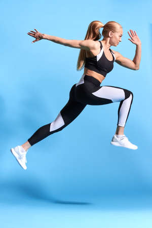 strong sportswoman taking part in the competition, isolated blue background, studio shot.strength, body and health care. wellness, wellbeing.