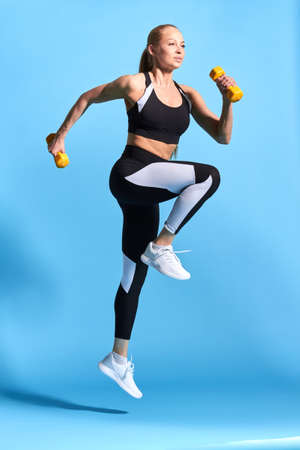 pleasant beautiful woman in stylish sportswear working out with dumbbells. full length photo. isolated blue background.motivation, long jump. body care. health care