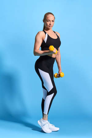 slim sporty beautiful blonde woman doing exercises with small dumbbells, developing muscles isolated over blue background. full length photo. studio shot.