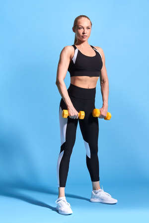 ,Young slim girl in sports clothes makes deadlift with weights isolated blue background. studio shot. full length photo. health and body care. wellness, wellbeing