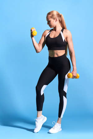 athletic beautiful girl with raised arms doing fitness workout with dumbbells on blue studio background sport and health care. full length photo