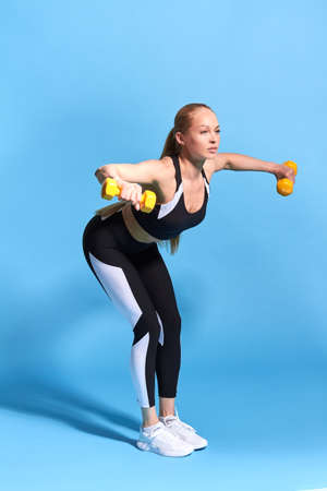 fit fair-haired girl doing bending exercises. side view full length photo. health and body care. free time, spare time