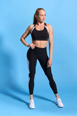 confident serious beautiful woman with ponytail looking away while standing in blue studio. full length photo. health and body care, wellness, hobby.