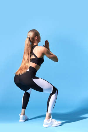 young slim woman doing squat. isolated blue background. studio shot. health and body care 免版税图像