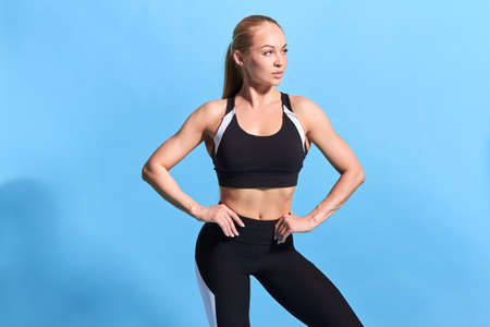 blond beautiful lovely girl with hands on the hips looking aside, having a rest during training. close up photo. isolated blue background