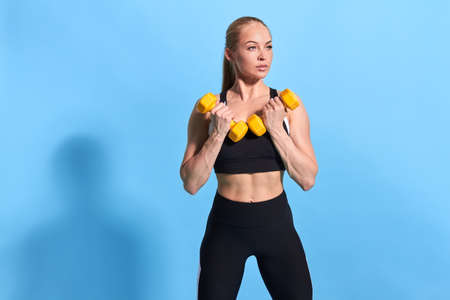 confident serious good looking sportswaomn working out with yellow dumbbells, isolated blue background. studio shot. free time, hobby