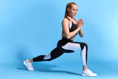 slim attractive lovely girl keeping palms in front of the breast. doing cross fit exercises . full length side view photo. copy space