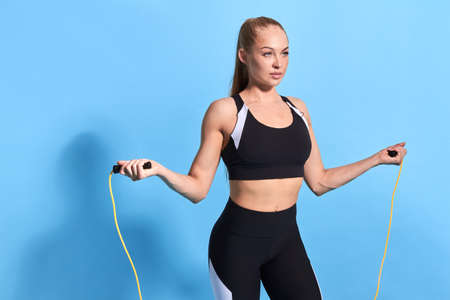 pretty sexy awesome blonde woman keeps fit. wellness, wellbeing, losing weight with skipping rope. sport equipment. close up photo. isolated blue background Banque d'images
