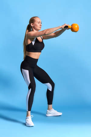 young attractive female sportswoman doing kettle bell exercise on blue background. Fitness girl working out. Crossfit, full length side view photo 免版税图像