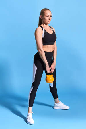 pleasant young sportswoman working out with weight. full length side view photo. isolated blue background. hobby, interest, lifestyle