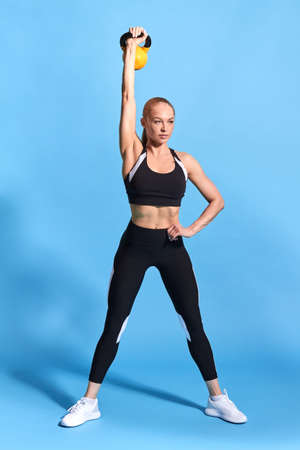 fit slim girl with a hand on his hip, wide legs raising the weight. full length photo. isolated blue background, strength concept. motivation, health and body care