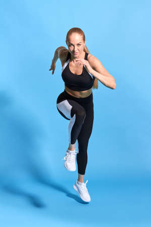 active hardwoking sportswoman running very fast, reaching the goal, acievement concept. success. isolated blue background. studio shot. full length photo