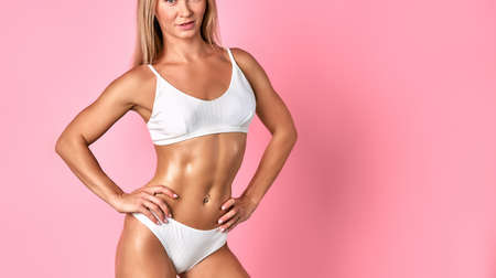 Sportive fit woman with tanned soft depilated skin, demonstrating beautiful white underground Banque d'images
