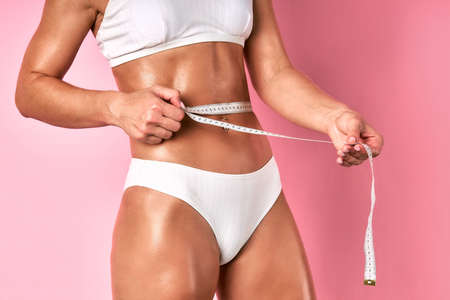 Slim tanned healthy body with flat beautiful torso, gentle hands holding long measure tape, wearing cotton lingerie, demonstrating wellbeing and beauty, close view, indoor shot