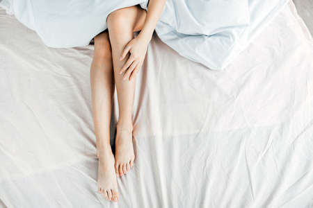 slim long legs. top view photo. girl is massaging her legs while lying on the bed. . cream for legs Banque d'images