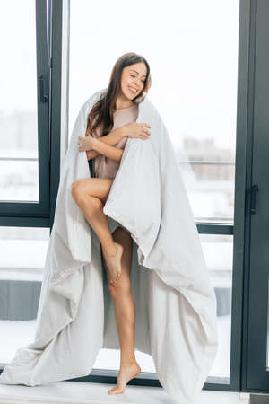 emotional sexy girl is posing to the camera. full length photo. happiness, grace, gracefullness. good looking girl wrapping in the white blanket