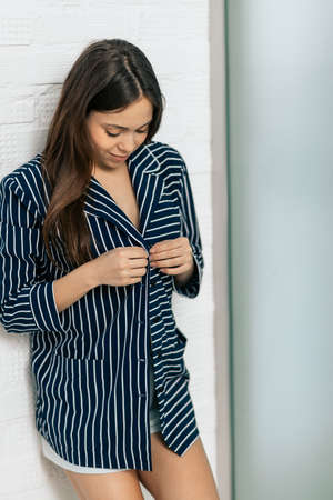 Young woman putting on striped pajama before going to bed. close up photo. preparation for sleep, fashion, style , clothes, woman put on a shirt