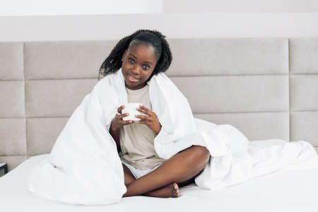 happy beautiful woman enjoyingmorning coffee in the bed at home. girl with blanket on her shoulders is holding a cup of tea
