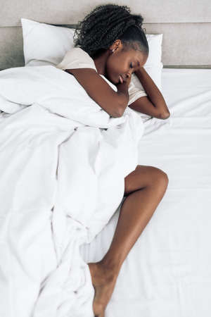 awesome african girl with wavy curly hair sleeping in her bed at night.night dream
