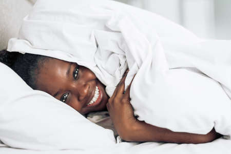 positive afro girl hiding under blanket.close up photo. favourite hobby