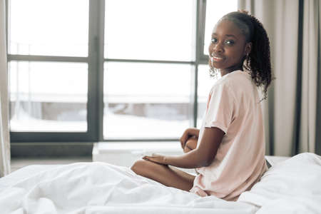 happy good looking girl is sitting on the bed and looking back. close up back view photo.copy space.beauty. people