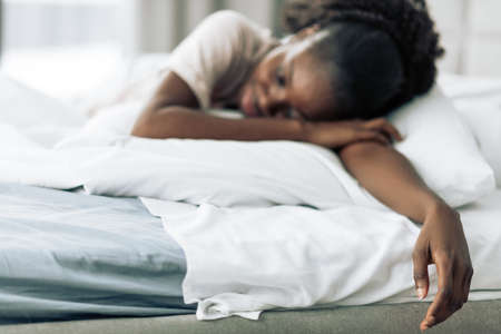 woman lying on her stomach on white comfortable bed. close up photo. blurred image. focus on hand . death, suicide.