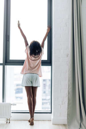 sim woman standing near the window and stretching. back view photo. greeting new day. Good morning