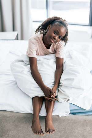 good looking girl sits on the edge of the bed in the morning and looking at the camera. close up photo. rest, free time. awesome woman with a pillow on her knees os pposing to the camera