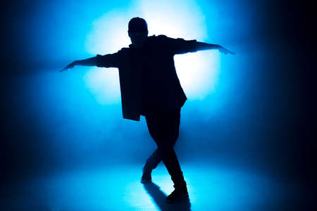 Sporty modern style hip-hop dancer dressed in urban style wear shows his dance on blue studio background.