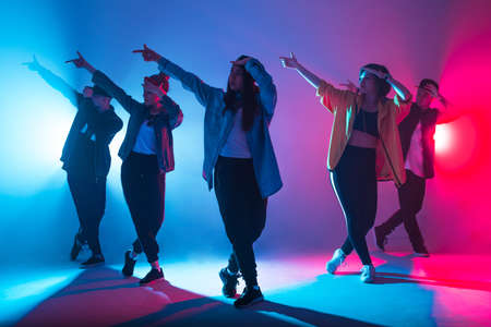 Animation group of young women and men dancing over red and blue dual color light on dark background