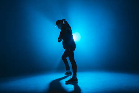 Silhouette of man giving solo performance, dancing alone in hip hop style on club scene with blue neon lightning and smoke.