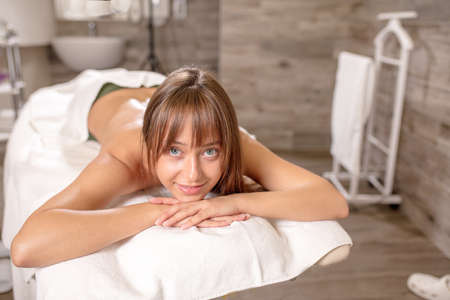 young pleasant cheerful girl waiting for a masseur. health , treatment, wellness concept. close up photo