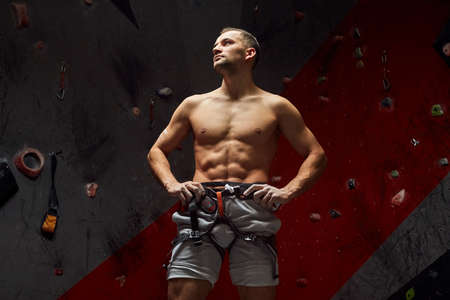Portrait of muscular rock climber posing with naked fit torso and equipped with belay system at indoor climbing gym