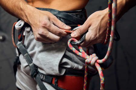Rock wall climber wearing safety harness, attaches safety hooks, ready to workout indoor, close-up.