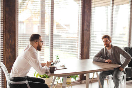 Indoor shot of two young bearded men in office wear, sitting at a table opposite each other. Employer is interviewing the job seeker