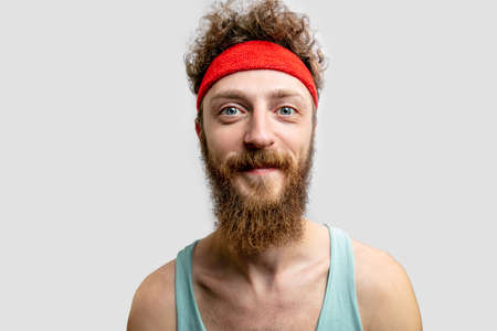 Cheerful man with red headband looking at camera. 免版税图像