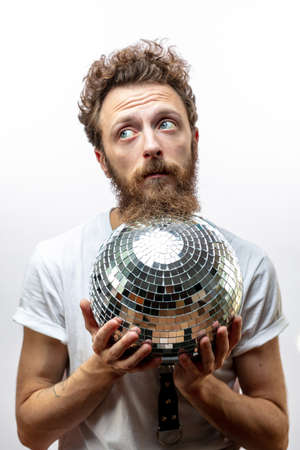 DJ man holds a disco mirror ball looking aside . Imagens