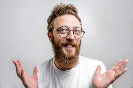 Friendly positive man wearing spectacles looking at camera with doubting, optimistic, questioning expression. Фото со стока
