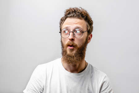 Emotional surprised bearded man looks with bated breath and shocked expression, keeps mouth widely opened, being afraid of something, isolated over white background. Body language and Emotions Reklamní fotografie