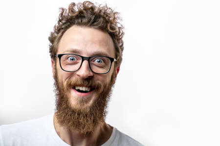 surprised bearded man in spectacles, looks with bated breath and shocked expression, keeps mouth widely opened, being afraid of something, isolated over white background. Body language and Emotions