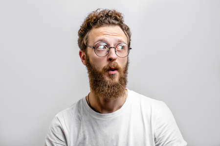 Surprised caucasian man with curly hair and beard stares in amazement aside, dressed in casual white t shirt, isolated over white background with copyspace. People, emotions reaction concept Reklamní fotografie