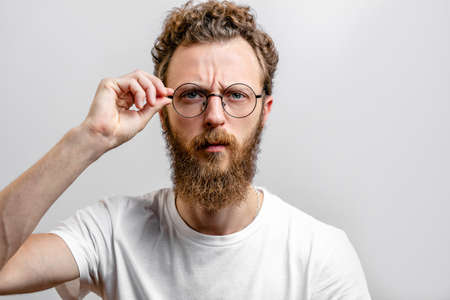 Headshot of serious bearded ners, scientist, with mustache and beard, wears round spectacles, has stylish hairdo, looks confidently. Reklamní fotografie